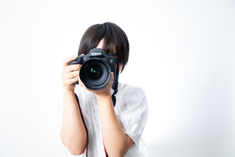 横向きにカメラを構える人