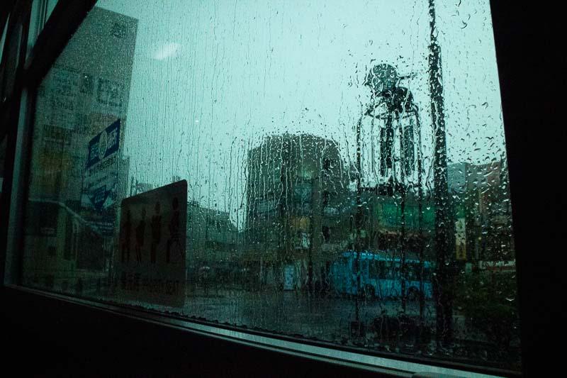 雨に濡れた窓ごしの風景